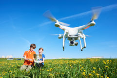 Children operating of flying drone at sunset. Boy and girl together operating drone flying or hovering by remote control in field stock images