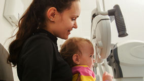 Children ophthalmology - mother and little girl - optometrist Checks Child`s Eye Royalty Free Stock Image