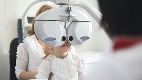Children ophthalmology - optometrist Checks Eye of little girl. Close up stock image