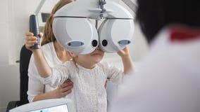 Children ophthalmology - optometrist Checks Eye of little girl Stock Photos