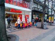 Children in orange vests walking in the center of Prague stock photography