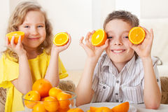 Children with oranges. Happy little girl and boy with fruit at home Royalty Free Stock Photos