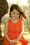 Children- Organge Girl. Little girl sitting in a tree for a portrait with her hair blowing Stock Images