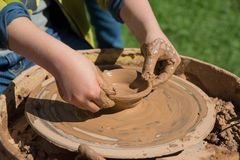 Children outdoor studying using pottery wheel Stock Photos