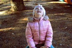 Wooden playground equipment with slides at autumn time. Happy blond girl child laughing and looking UP. royalty free stock photography
