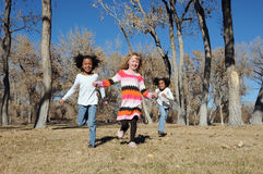 Children outdoors. Happy children running in the forest/park outdoors Stock Photos