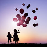 Children Outdoors Holding Balloons Together Concept Stock Photos