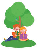 Children outdoors reading a book Royalty Free Stock Photography