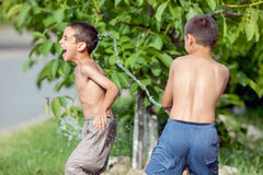 Children outside on a summer day, sprayed with balloons filled w Royalty Free Stock Photography