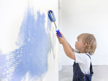 Children paint indoors. Happy children paint wall indoors Stock Photo