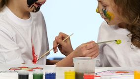 Children paint with paint on their clothes. White background. Slow motion stock footage