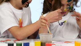 Children paint with paint on their clothes. White background. Slow motion stock video footage