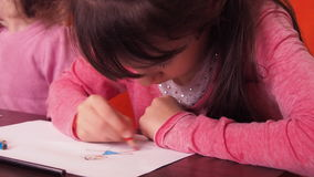 Children paint pencils. Two little girls draw on paper with crayons. stock footage