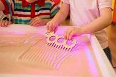Children paint in the sand, sand animation. Children paint in the interactive sand table , sand animation Stock Photography