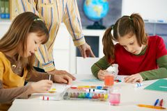 Children painting in art class. Elementary age children sitting around desk enjoying painting with colors in art class at primary school classroom stock photos