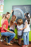 Children painting with chalk on. Blackboard together with a nursery teacher Stock Image