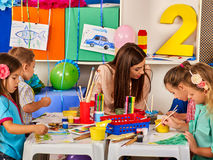 Children painting and drawing. Craft lesson in primary school. Children painting and drawing in kids club. Craft lesson in primary school. Kindergarten teacher Royalty Free Stock Images
