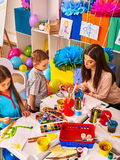 Children painting and drawing together . Craft lesson in primary school. Childrens paint brushes and children painting and drawing in kids club. Craft lesson in Stock Images