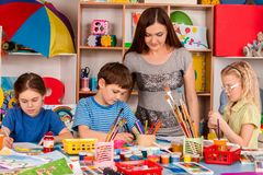 Children painting and drawing together. Craft lesson in primary school. Kids playroom organization of children painting and drawing in kid`s club. Hobby for Royalty Free Stock Photo