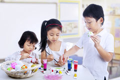 Children painting easter eggs in art class stock images