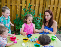 Children Painting Easter Eggs Outside with Mom Royalty Free Stock Images