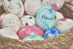 Children painting easter eggs with their mom`s help and with markers at home stock photography