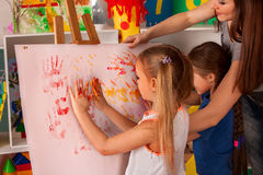 Children painting finger on easel. Group of kids with teacher. Royalty Free Stock Photo