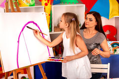 Children painting finger on easel. Group of kids with teacher. Royalty Free Stock Photography