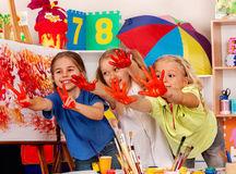 Children painting finger on easel. Small students in art school class.