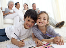 Children painting on floor with family in sofa Stock Photo