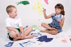Children painting pictures. Two children are painting pictures on a large white sheet of background paper Stock Photos