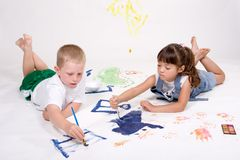 Children painting pictures. Two young children are lying down and painting pictures on a large white sheet of background paper Stock Image