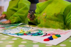 Children painting with pinger paint. Oon white paper Royalty Free Stock Photography