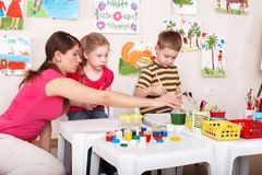 Children painting with teacher in art class. Royalty Free Stock Photos