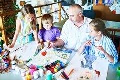 Children Painting with teacher in Art Class royalty free stock photo