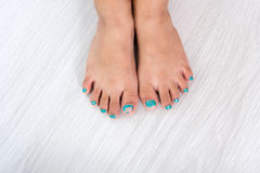 Children painting toe nails / pedicure on grey Royalty Free Stock Photography