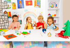 Children painting together New Year balls and sit Stock Images