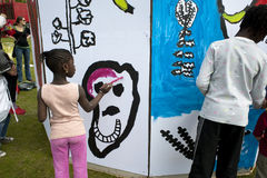 Children Painting Wall Mural. African Children  Painting Wall,  ,  on the Lawn at La Villette , Paris, France Stock Photo