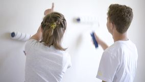 Children painting wall in room. Teen boy and girl makes repairs in new flat. Sister and brother painting wall in apartment room. Children paints the wall, using stock video footage