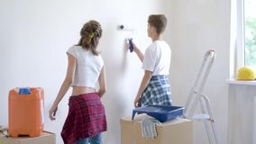 Children painting wall in room stock video footage