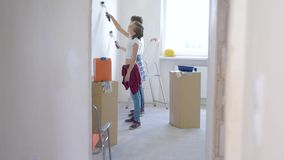 Children painting wall in room. Teen boy and girl makes repairs in new flat. Sister and brother painting wall in apartment room. Children paints the wall, using stock footage