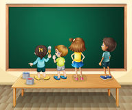 Children paintinging the blackboard in the room Stock Image