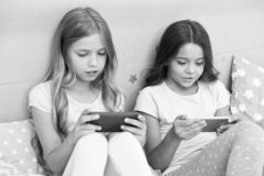Children in pajama interact with smartphones. Application for kids fun. Internet surfing and absence parental advisory. Smartphone internet access. Girls royalty free stock photos