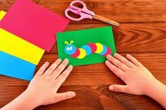 Children paper applique - colored caterpillar on green sheet. Kids summer crafts Royalty Free Stock Photos