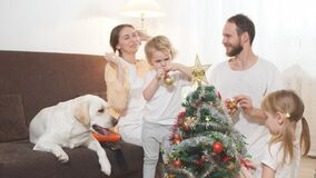 Children and parents decorating christmas tree at home