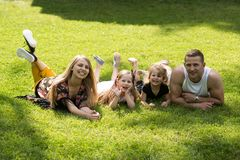 Children and parents lie on green grass. Girls, women and men smile on summer landscape. Mothers and fathers day. Happy childhood, family, love. Vacation royalty free stock photos