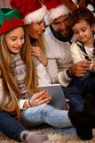 Children with parents looking Christmas photos Royalty Free Stock Photography