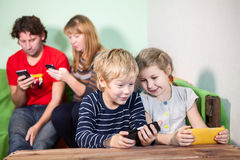 Children and parents playing games on smartphones Royalty Free Stock Photos
