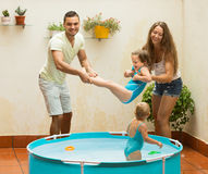 Children and parents playing in pool Stock Image