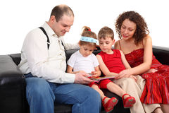 Children with parents read book on sofa Stock Photo